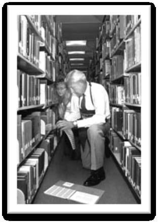 The first efforts in Carlson Library's automation project required that each book in the library's holdings have a barcode attached. President Horton showed his support for the project in 1991. (Photo by Liz Brandt.)